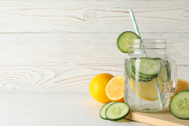 Glass jar with cucumber water on board, space for text