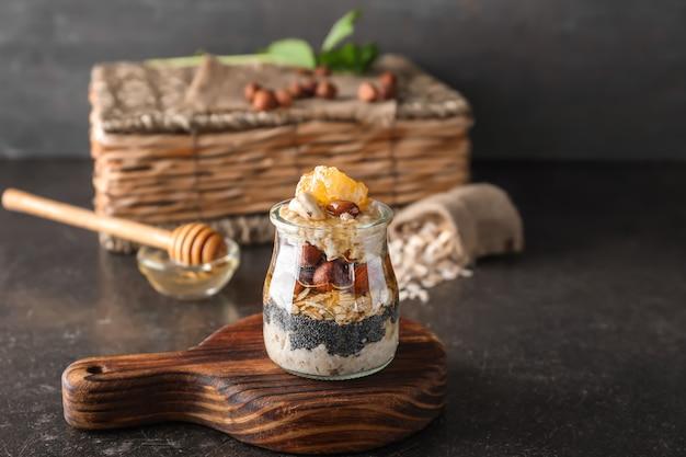 Стеклянная банка с вкусным овсяным десертом на столе