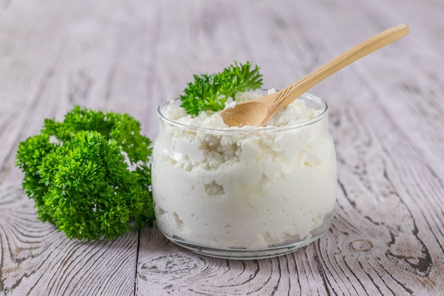 신선한 코티지 치즈와 파슬리 유리 항아리는 나무 테이블에 나뭇잎. 건강한 식단의 개념.