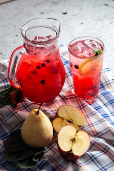 Glass and a jar with fresh fruit red lemonade with napkin and pear