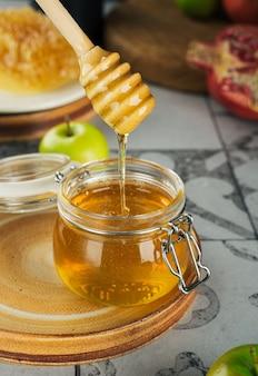 신선한 꿀 꿀 숟가락 사과와 석류 개념 유태인 새해 해피 홀리데이와 유리 항아리