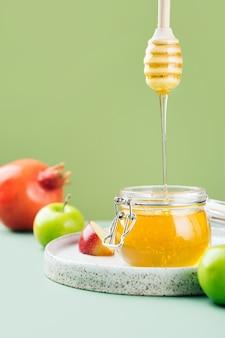 밝은 녹색 배경창에 신선한 꿀 꿀 숟가락 사과와 석류가 있는 유리 항아리