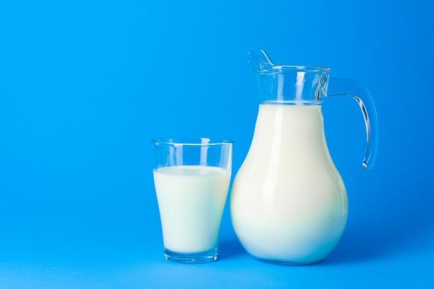 파란색 배경에 신선한 우유와 유리 항아리를 닫습니다.