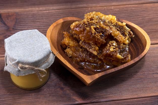 蜂蜜と木製の背景にハニカムの蜂蜜と木の板とガラスの瓶