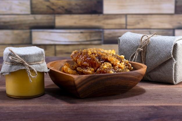 Стеклянная банка с медом и деревянная тарелка с медом в сотах на деревянном фоне