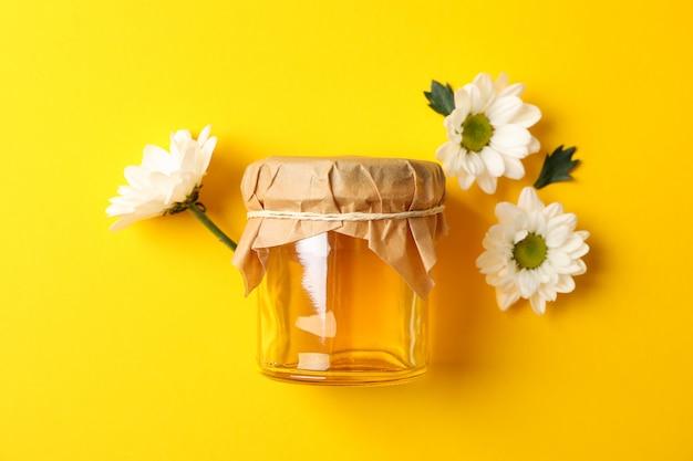 蜂蜜と黄色の背景、テキスト用のスペースにカモミールのガラスの瓶