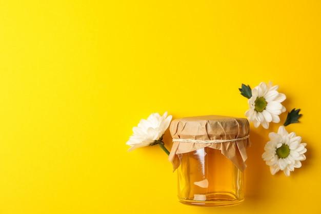 蜂蜜と黄色の背景にカモミールのガラスの瓶