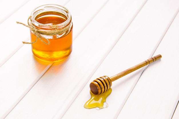 白い木製のテーブルの背景に蜂蜜とディッパーとガラスの瓶。