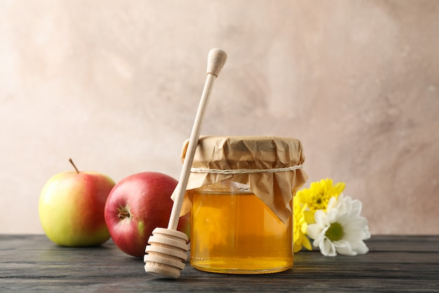 Стеклянная банка с медом, ковшом, яблоками и цветами на деревянном фоне