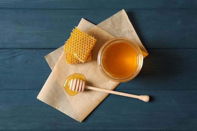 蜂蜜、ひしゃく、ハニカム、木製の背景、コピー領域の羊皮紙が付いているガラス瓶