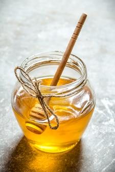 蜂蜜入りガラス瓶。石の背景に。