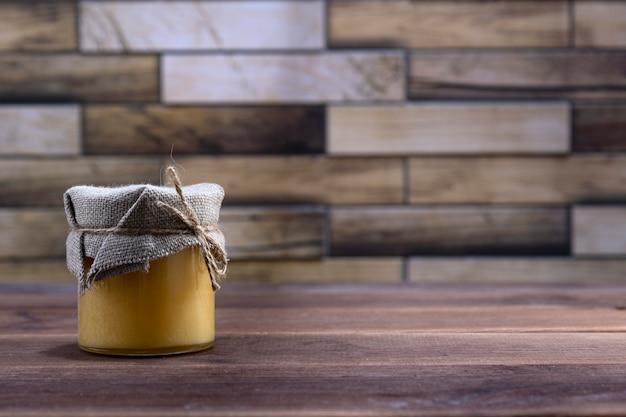 テキストのための場所で木製の背景の上に蜂蜜が付いているガラス瓶