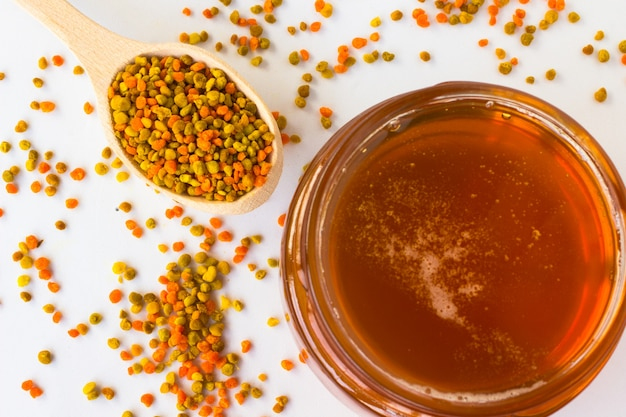 Glass jar with honey and pollen in a wooden spoon on a white space.