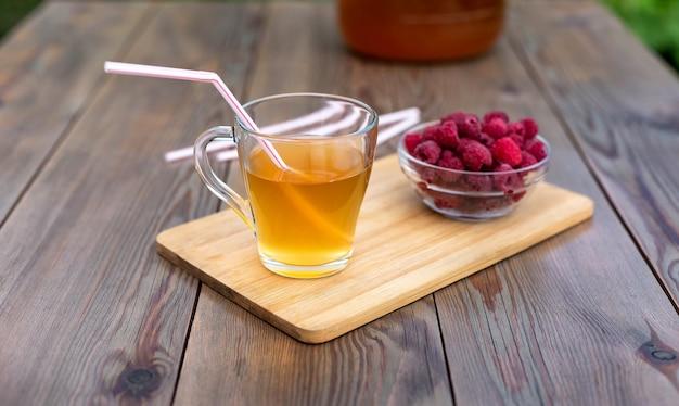 Стеклянная банка с чайным грибом, стакан с чайным грибом и малиной в летнем саду