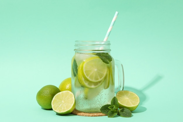 Glass jar with lemonade and ingredients on mint surface
