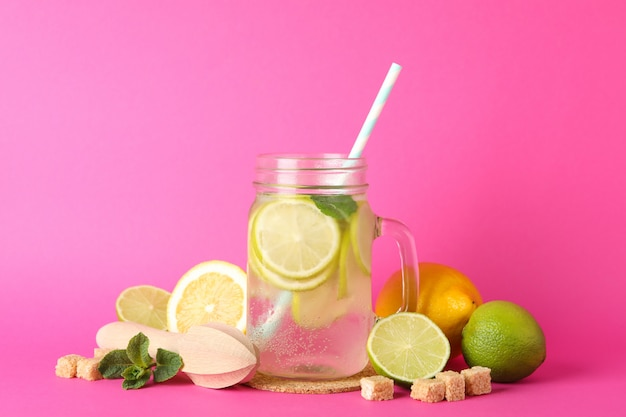 Glass jar with lemonade and ingredients on pink surface