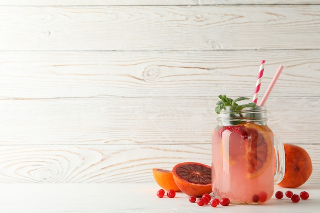 Glass jar with lemonade and ingredients on wooden surface