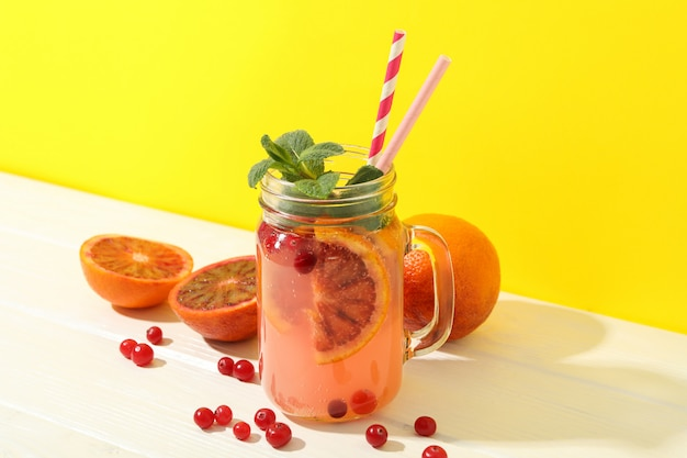 Glass jar with lemonade and ingredients on wooden table. fresh drink