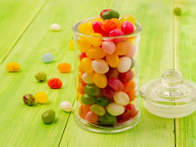 Glass jar with lid filled with colorful candies on green background, many jelly bean scattered