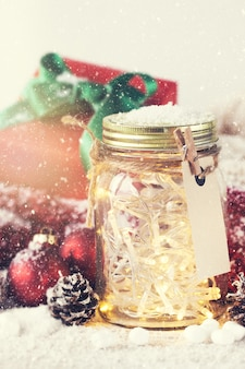 Glass jar with lights and christmas decorations with snow around