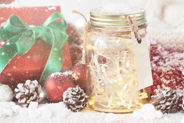Glass jar with lights and christmas decorations with snow around Free Photo