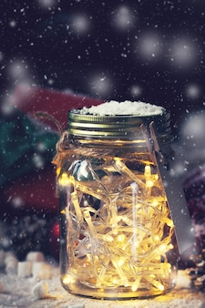 Glass jar with lights and snow on top