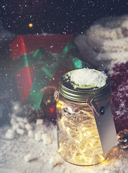 Glass jar with lights with a gift next to it while it snows viewed from above