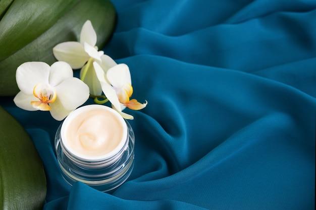 Стеклянная банка с увлажняющим, лифтинг-кремом и белыми цветами орхидеи фаленопсис