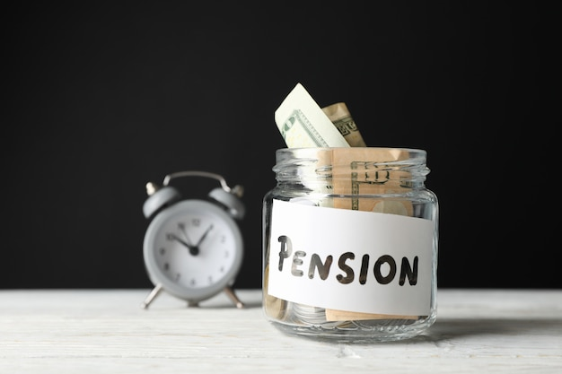 Glass jar with money and alarm clock against black, close up