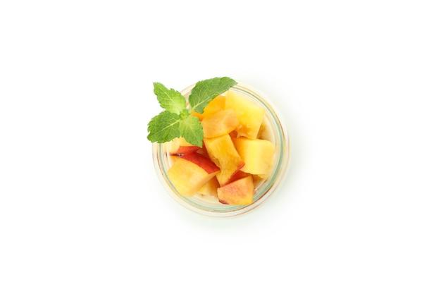 Glass jar with peach yogurt isolated on white background