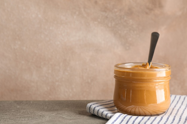 Glass jar with peanut butter and spoon, and kitchen towel on wooden table