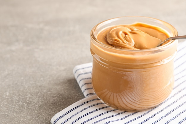 Glass jar with peanut butter and spoon, and kitchen towel