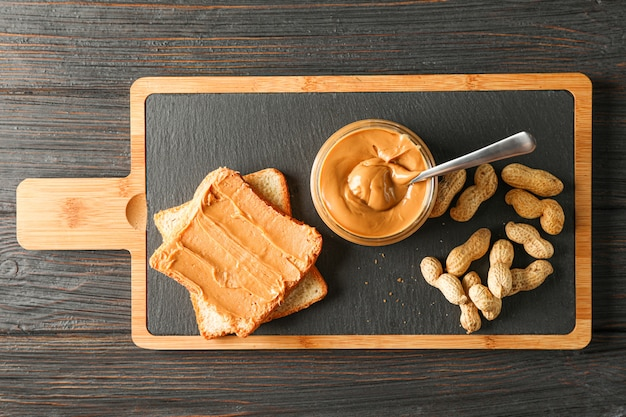 Glass jar with peanut butter and spoon, peanut, peanut butter sandwich and cutting board on wooden table, space for text and top view