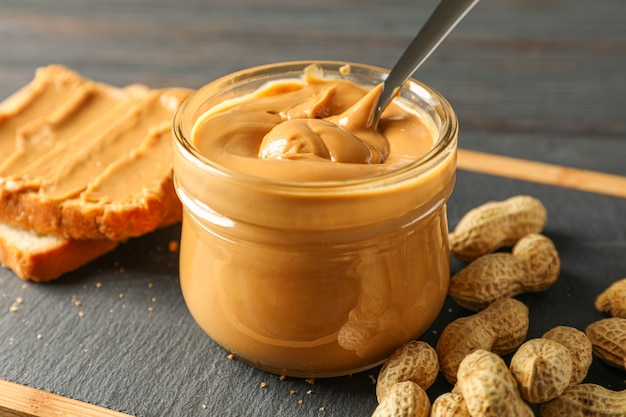 Glass jar with peanut butter and spoon, peanut, peanut butter sandwich and cutting board on wooden table