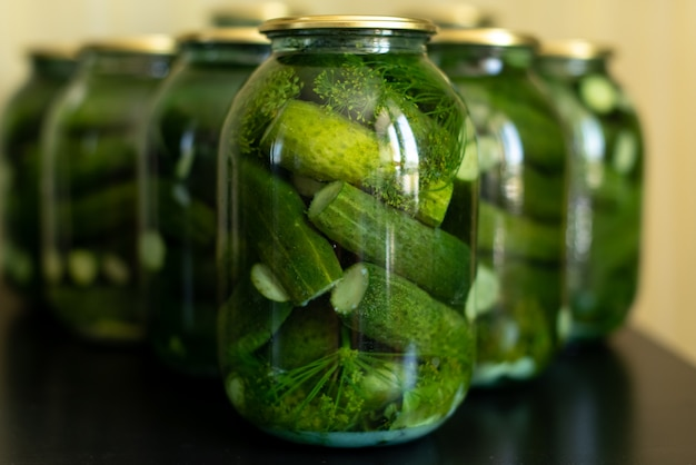 Glass jar with pickled cucumbers on gray