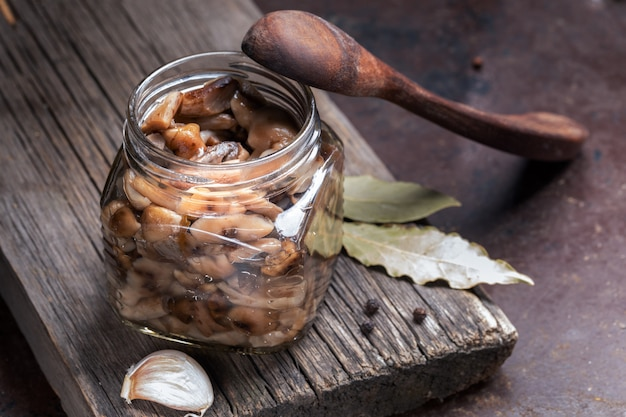 Glass jar with pickled forest honey agarics, wooden spoon and spices on old wooden board