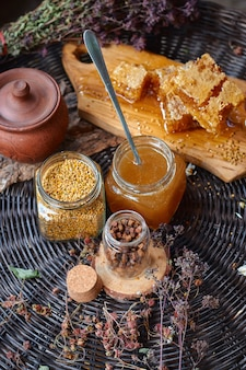 A glass jar with pollen, honeycomb honey, and propolis on a wooden board stands on a wicker table