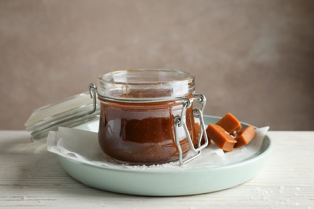 Glass jar with salted caramel and candies on wooden space, space for text
