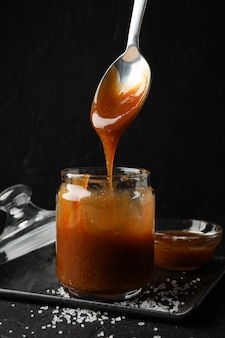 Glass jar with salted caramel and spoon on black space, copy space