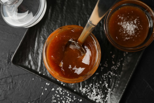Glass jar with salted caramel and spoon on black space, top view