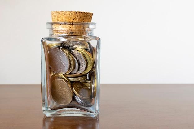 Стеклянная банка с несколькими монетами и пробковой крышкой. концепция экономики и финансов.