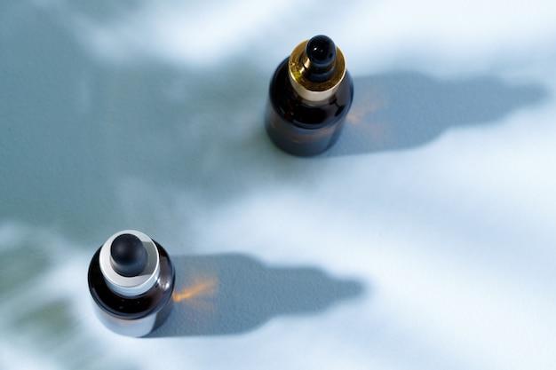 Стеклянная банка с жидкостью для ухода за кожей на сером фоне с тенью