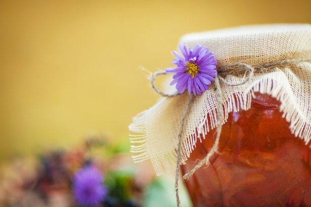 Glass jar with tasty apricot jam on a table. autumn time