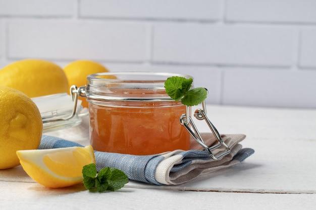 Стеклянная банка с вкусным лимонным джемом на белом деревянном столе