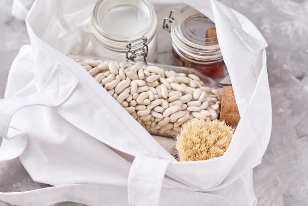ガラスの瓶、木製のブラシ、白い背景の上の買い物袋。廃棄物ゼロのコンセプト。プラスチック製の道具なしでキッチンの背景