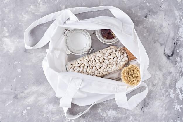 ガラスの瓶、木製ブラシ、白のショッピングバッグ。廃棄物ゼロのコンセプト。プラスチック器具のないキッチン
