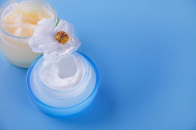 Glass jars of beauty cream with white flower on the blue background. top view. copy space.
