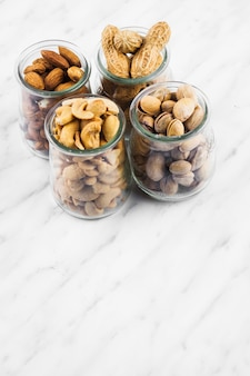 Glass jars filled with nut food on marble backdrop
