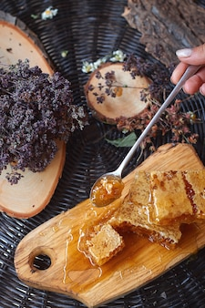 緑の葉に対する蜂蜜のガラス瓶、健康的な朝食のコンセプト、クローズアップ