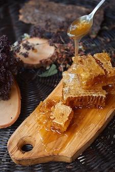 緑の葉に対する蜂蜜のガラス瓶、健康的な朝食のコンセプト、上面図